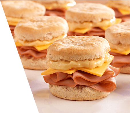 Close up of ham and cheese breakfast sandwiches served on flaky biscuits