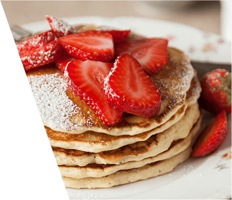 An close up of a stack of pancakes topped with powdered sugar and strawberry slices