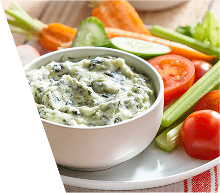 A bowl of spinach dip with fresh veggies