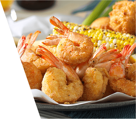 Plate of batter fried shrimp served with corn on the cob