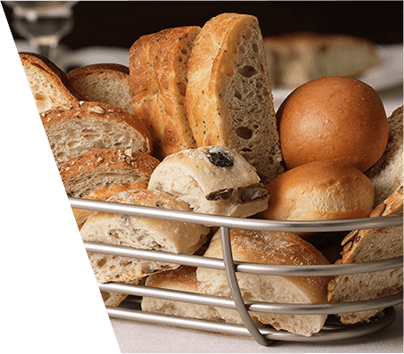 A metal bread basket filled with various artisanal breads and rolls