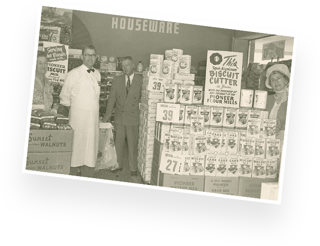 Historical shot of people gathered around a display of Pioneer biscuit mix in a grocery store