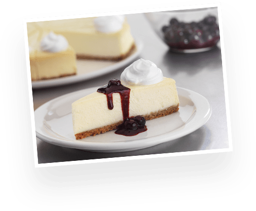 A slice of cheesecake drizzled with blueberry sauce.