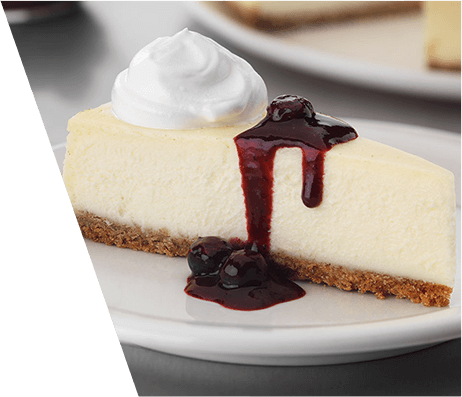 A slice of cheesecake with a dollop of whipped cream and a blueberry sauce drizzle