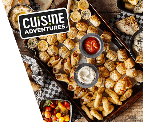 Overhead view of backing tray covered with various and Cuisine Adventure logo